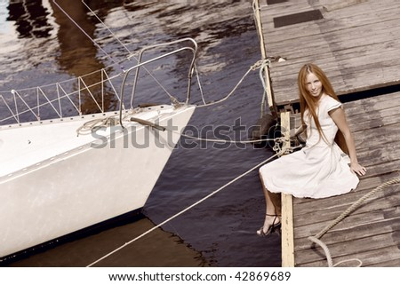 The image of a beautiful girl on the pier - stock photo