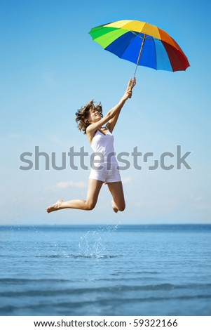 The image of a beautiful girl who jump with a rainbow umbrella - stock photo