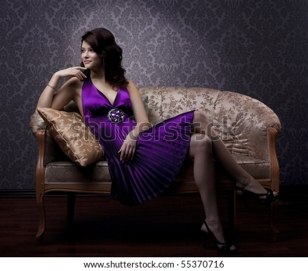 The image of a beautiful luxurious woman sitting on a gold vintage couch