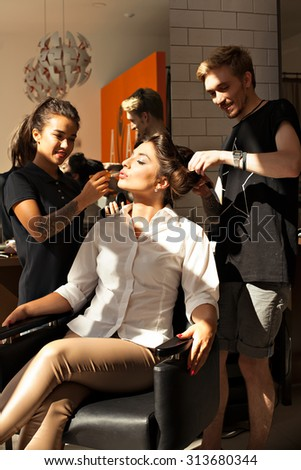 The image of a beautiful young brunette girl model sitting in a chair in a beauty salon with a hairdresser and makeup artist. Stylist- hairdresser and stylist, makeup artist working - STOCK PHOTO - stock photo