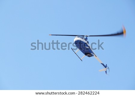 The image of a flying helicopter - stock photo