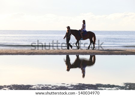 The image of a girl riding a horse on the background of the sea