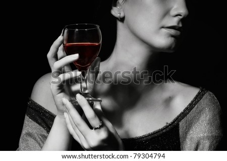 The image of a glass with a red wine in a female hand - stock photo