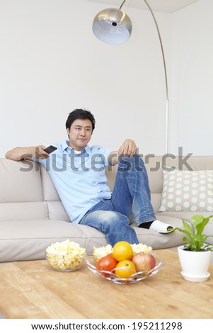 the image of a happy Asian father eating popcorn - stock photo
