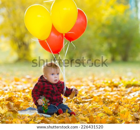 The image of a little child with a bunch of balloons in their hands in yellow autumn park - stock photo