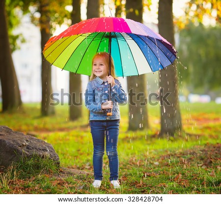 The image of a little girl with a rainbow umbrella in park - stock photo