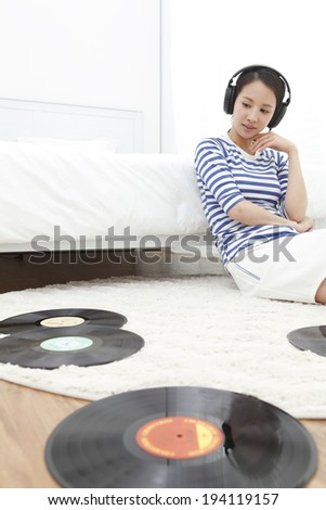 the image of Asian woman listening to vinyls