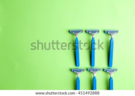The image of blue razor blades ona a green bakground.