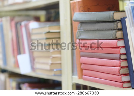The image of books on the shelf in a library. The books on the background are blurred - stock photo