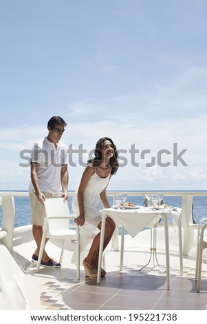 the image of couple having dinner by the beach