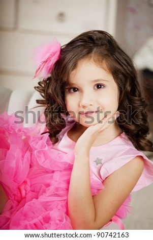 The image of girl in the nursery in pink dress