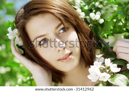 The image of the beautiful girl in the garden among the blooming trees