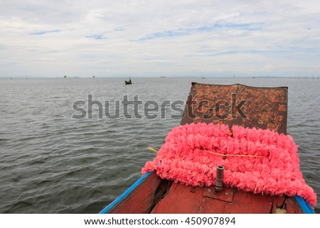 The image of the bow of a fishing shoreline is decorated with a garland out to fish in the sea in Thailand. - stock photo