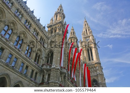 The image of the clock tower on blue sky background. In the foreground an old building with flags of Austria. Vienna.