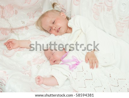 The image of the girl and its newborn sister - stock photo