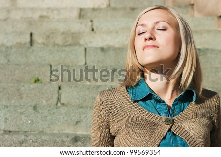 The image of the girl of a granite ladder sitting on steps - stock photo