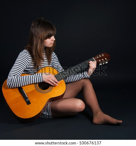 The image of the girl with a guitar on a black background