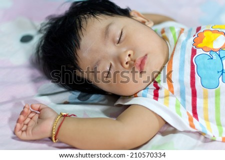 The image of the newborn baby girl lying on the bed Asian - stock photo
