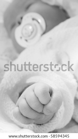 The image of the newborn child. Focus on a hand
