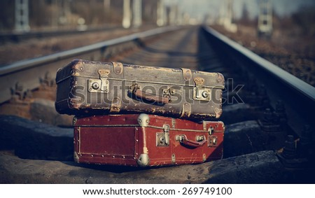 The image of two old vintage suitcases forgotten on railway tracks. - stock photo