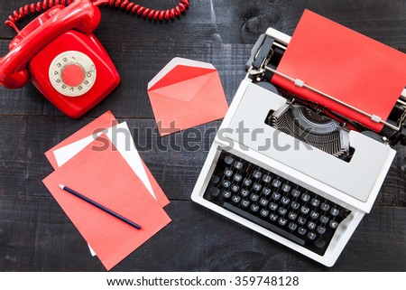 The image represents a retro typewriter  and some colored paper on a dark wood background with a red paper conceptualizing this colour like danger, love or something different - stock photo