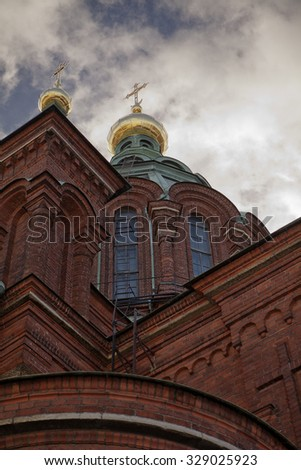 The imposing brick facade, central dome and golden cross of the Uspenski Cathedral, a Russian Orthodox church, in Helsinki, Finland.