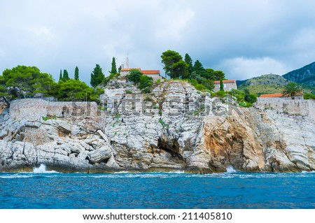 The impregnable rocks of the Sveti Stefan island with the small church, scenic garden and the hotel complex on the top, Montenegro. - stock photo