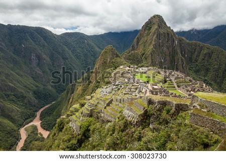 The Incan ruins of Machu Picchu , Peru. UNESCO World Heritage Site. Cloudy sky and Urubamba river background - stock photo