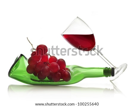 The inclined wineglass of red wine and the deformed bottle with grapes isolated over white. - stock photo