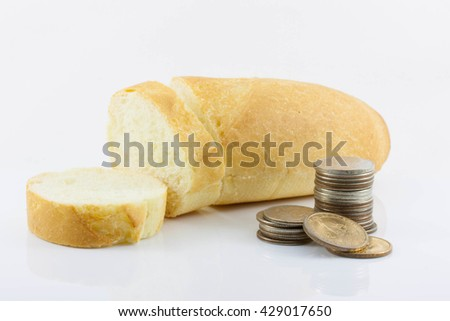 the increase in bread prices, the rising cost of bread, inflation, crisis, isolated. Handful of coins and sliced bread on white background - stock photo