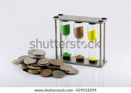 The increase in the price of labour, the growth of the man-hour cost, time cost, inflation, crisis, isolated. a handful of coins and hourglass on a white background - stock photo
