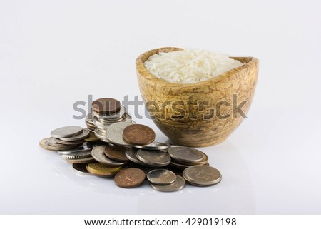 The increase in the price of rice, the rising cost of rice, inflation, crisis, isolated. a handful of coins and white rice on a white background - stock photo