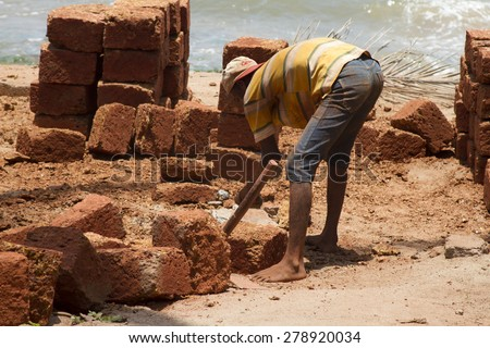 The Indian man works at building. India Goa. - stock photo