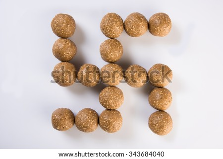 The indian sesame sweet or tilgul laddu, made up of jaggery and sesame seeds, hand made, round, indian sweet on Makar Sankranti festival, swastik formation, hindu holy symbol top view on white back - stock photo