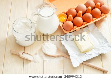 the ingredients for the dough , eggs , milk, butter , salt and flour on a wooden background