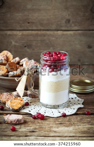The ingredients in a glass jar for making cranberry shortbread. For original gift. Selective focus. - stock photo