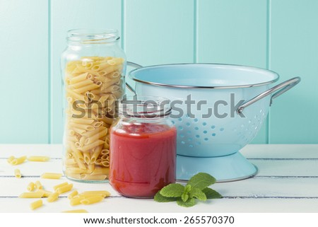The ingredients to cook macaroni: pasta, tomato and a turquoise strainer on a white wooden table
