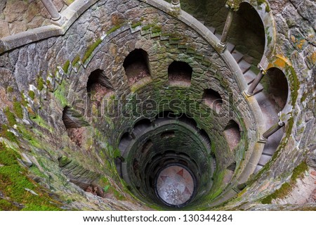 The Initiation well of Quinta da Regaleira in Sintra, Portugal. It's a 27 meter staircase that leads straight down underground and connects with other tunnels via underground walkways. - stock photo
