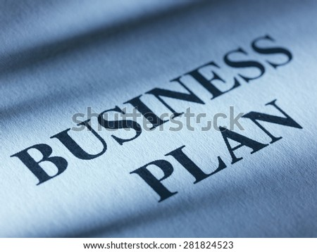 "The inscription ""business plan"" on a sheet of blue paper.Close up"