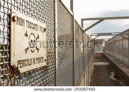 The inscription in Italian. Warning sign on the bridge over the railway. Carefully electricity. - stock photo