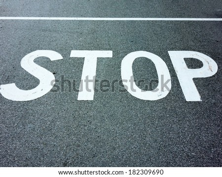 the inscription stop on a road. stopping at an intersection because of stop sign. - stock photo