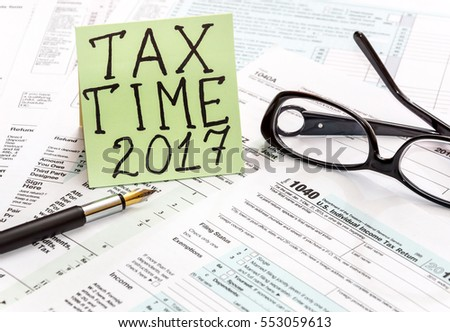 "The inscription ""Tax time 2017 "" on the sticker, pen and glasses on tax forms."