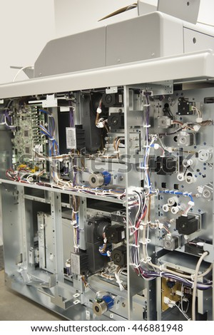 The inside of a sophisticated digital press copier revealing a collection of gears, wires and circuit boards - stock photo