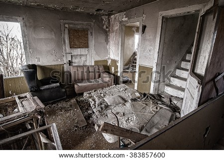 The inside of an abandoned house. This house has been abandoned for years and is showing the signs of vandalism and deterioration. - stock photo