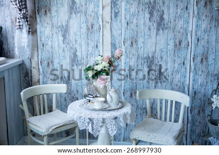 The interior in blue tones with two chairs and a vase with flowers. On the table are a kettle and a cup of tea. Wall of old boards - stock photo