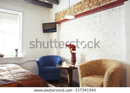 The interior of a cozy studio-type guest house, armchairs ant TV set  - stock photo