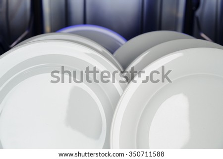 the interior of a dishwasher after a finished rinsing cycle with cleaned white plates