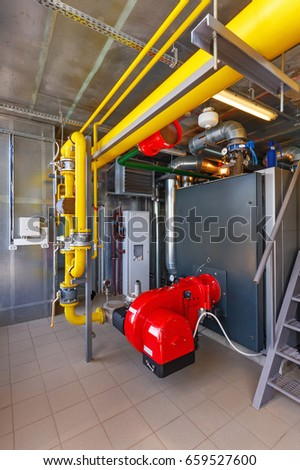 The interior of a modern gas boiler house with boilers, pumps, valves and a multitude of sensors.