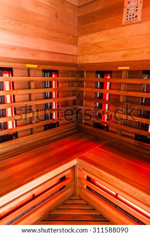 the interior of a small wooden infrarered sauna booth in a spa - stock photo