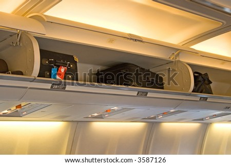 The interior of an airplane cabin with seats, passengers and baggage - stock photo